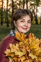 A mature woman holding a bunch of autumn leaves in nature