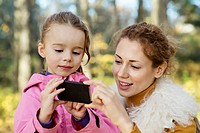 A young daughter showing her Mom something on a smart phone