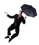 Businessman holding an umbrella and jumping