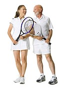 Senior couple standing with tennis rackets