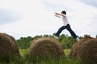 Profile of a boy leaping on hay bales