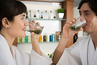 Close_up of a young couple drinking wheatgrass juice