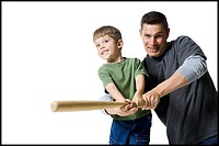 Portrait of a father teaching his son how to swing a baseball bat