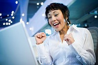 Low angle view of a businesswoman laughing in front of a laptop