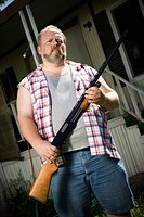 Overweight man with a shotgun