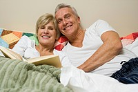 Mature couple in bed reading