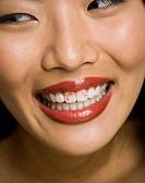 Closeup of woman smiling with red lipstick on teeth