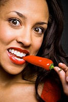 Woman with red lipstick eating red pepper