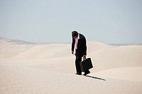USA, Utah, Little Sahara, mid adult businessman walking on desert
