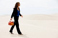 USA, Utah, Little Sahara, young businesswoman walking on desert carrying gas can