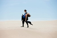 USA, Utah, Little Sahara, mid adult businessman carrying young woman on desert