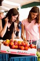 Women shopping for fruit at an outdoor market