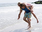 Man carrying woman in shallow water at the beach