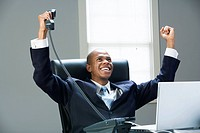 Businessman on laptop cheering