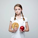 Studio shot of girl 10_11 holding cookie and red apple