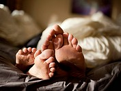 USA, Utah, Provo, Close_up of feet of couple lying in bed