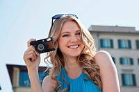 Young woman holding vintage camera