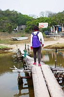 Asian woman walking along a wooden bridge