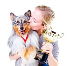 Beautiful young dog owner kissing her champion shetland sheepdog and a gold trophy