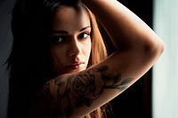 Sexy young hispanic woman with a tattoo gazing at you
