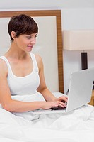 Smiling woman using laptop in bed