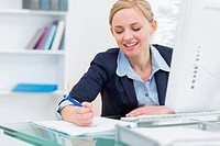 Business woman writing notes at desk in office