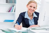 Smiling business woman writing notes at office desk