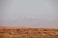 Ruins of stone buildings in foreground snow capped peaks of high Atlas Mountains in background, Sahara Desert, Morocco