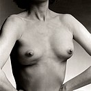 A woman performing her own breast exam has her arms on her hips, with the elbows out and pushed forward.