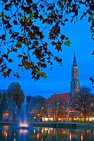 Martinskirche St Martin´s Church bell tower and a fountain fringed by trees along the bank of the Isar River, City of Landshut, Bavaria, Germany, Euro...