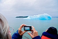 A sightseeing senior woman with a digital camera photographs ice from Le Conte Glacier, the southernmost tidewater glacier in the United States, near ...