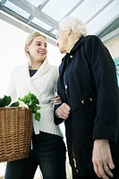 Young woman helps an elderly lady and carries the shopping