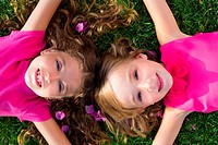 children friend girls lying together on garden grass smiling happy aerial view