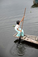 Close up of a Young Intha girl cruising in her canoe through the floating houses at the Inle Lake, Shan state, Myanmar, Burma