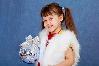 Little girl in white fur costume holding glass ball