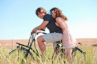 Couple riding bicycle in tall grass