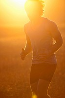 Man running in tall grass at sunset