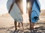 Two female surfers walking on beach