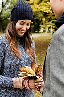 Couple holding autumn leaves