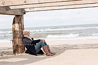 Woman sitting under abandoned pier