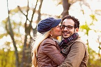 Smiling couple kissing in forest