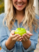 Mid_section of young woman holding green apple