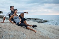 Couple relaxing on boulder by ocean