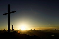 Hiker standing by cross on rocky hilltop