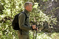 A mature man walking outdoors, holding walking poles and carrying a rucksack