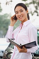 Chinese businesswoman holding notebook and talking on cell phone