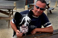 Calais France Man With Chinese Crested Dog At Picnic Table