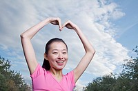 Chinese woman with arms raised making heart_shape