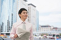 Chinese businessman holding newspaper outdoors