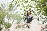 Chinese businesswoman standing on bridge
